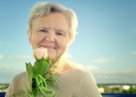 landlady: Senior woman smelling rose on blue sky.