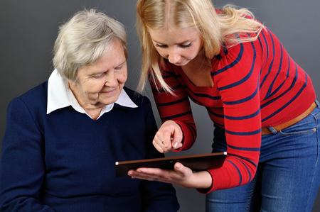 personas sentadas: Mujer joven aprende mujer mayor a utilizar la tableta. Foto de archivo