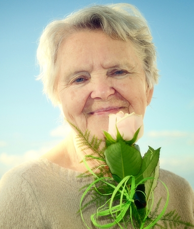 landlady: Senior woman smelling rose on blue sky.