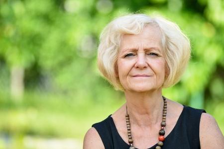 Mature, blonde woman in garden, Stock Photo