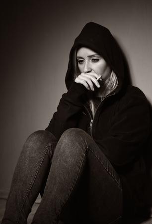 hooded sweatshirt: Rebellious teenager in a hooded sweatshirt smoking a cigarette. Stock Photo
