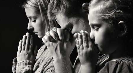 Modląc się rodzinę. Mężczyzna, kobieta i dziecko.