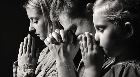 worship white: Praying family. Man, woman and child.