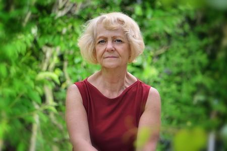 Mature, blonde woman in garden, Standard-Bild