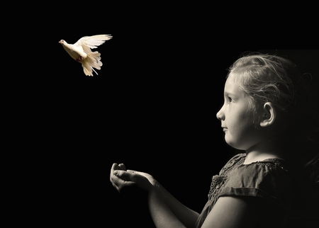 The little girl releasing a white dove from hands . Symbol of peace on a black background.