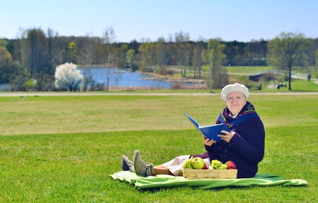 Senior happy woman sitting on a blanket on glade in the park. She is reading book. Healthy outdoor activities. Happy and smilling.