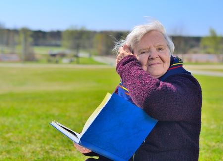 Senior happy woman sitting on on glade and reading book in the park. Healthy outdoor activities. Happy and smilling. photo