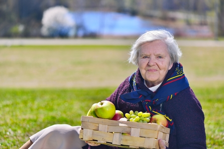 Senior happy woman sitting on on glade in the park. Healthy outdoor activities. Happy and smilling. photo