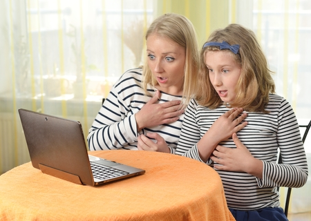 astonished: Happy girl and grandmother using a laptop in home.
