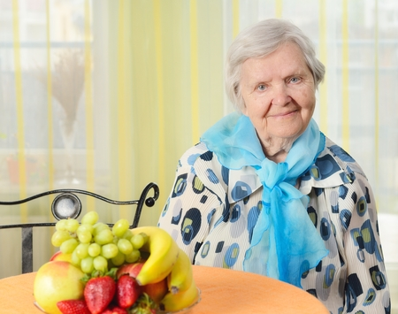 senility: Senior happy woman in her home with window on background.