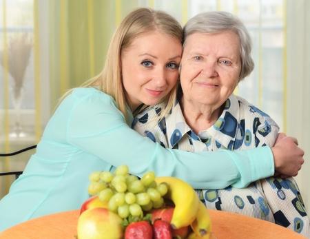 amigos abrazandose: Mujer mayor con su cuidador. Feliz y sonriente.