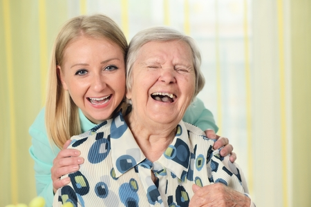old: Senior woman with her caregiver. Happy and smiling. Stock Photo