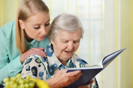 adult 80s: Senior woman with her caregiver in home reading book.