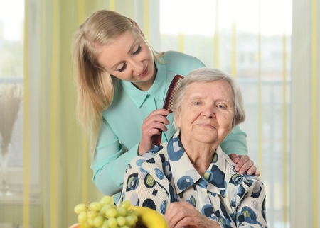 Senior woman with her caregiver in home. Imagens