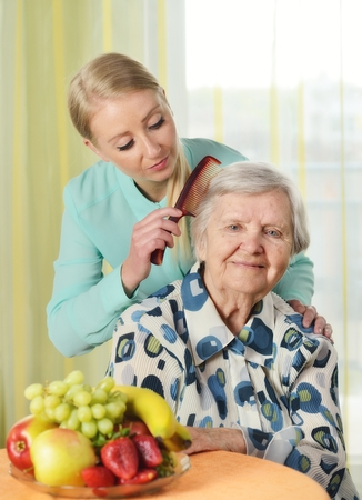 medical care: Senior woman with her caregiver in home. Stock Photo