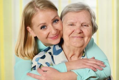 personas abrazadas: Mujer mayor con su cuidador. Feliz y sonriente.