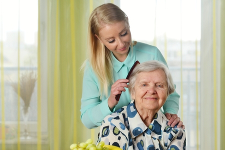 Senior woman with her caregiver in home. Reklamní fotografie