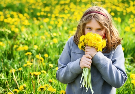 Young girl with bouquet of yellow flowers on meadow full of dandelions. photo