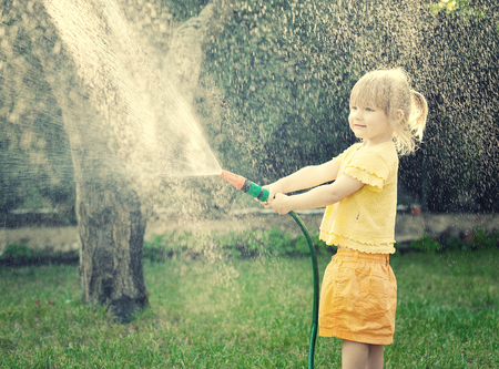 girl action: Little girl playing in the garden pouring all the water from a garden hose.