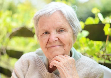 Senior gelukkige vrouw lachend in de tuin. Stockfoto