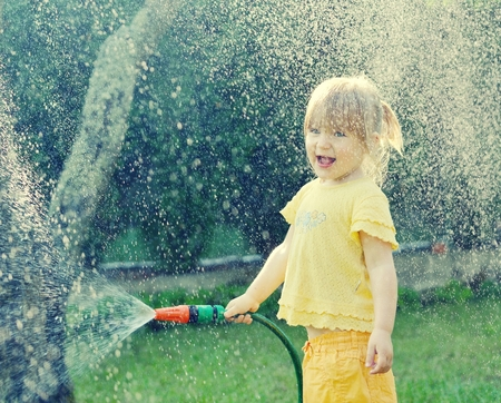 hot weather: Little girl playing in the garden pouring all the water from a garden hose.