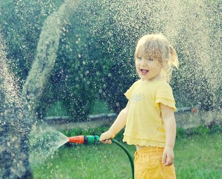 ni�as sonriendo: Ni�a que juega en el jard�n de verter toda el agua de una manguera de jard�n.