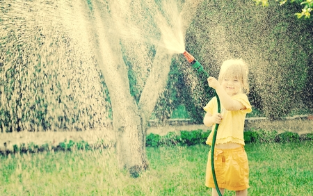 Little girl playing in the garden pouring all the water from a garden hose.