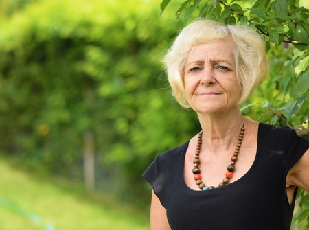 misses: Mature, blonde woman in garden, Stock Photo