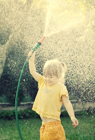 water garden: Little girl playing in the garden pouring all the water from a garden hose.