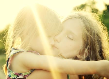back lighting: Two sisters Cuddled up together. Back lighting sunlight.