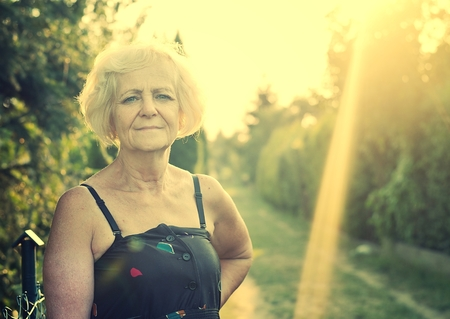 misses: Mature, blonde woman in garden, Vintage Style. Stock Photo