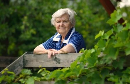 satisfaction: Senior happy woman smiling in garden.