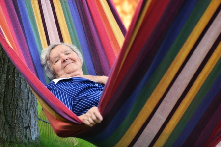 happy senior: Senior happy woman resting on a hammock in garden. Stock Photo
