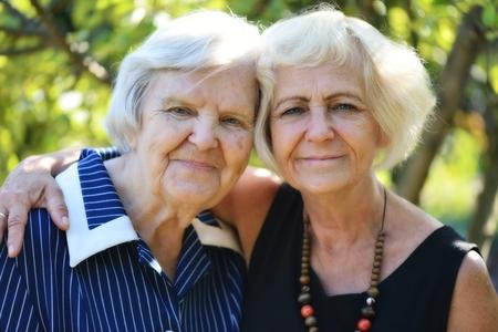madre e hija: Mujeres mayores y maduros en el jardín.