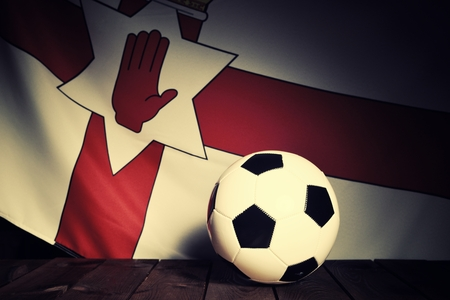 northern ireland: Flag of Northern Ireland with football on wooden boards as the background. Vintage Style.
