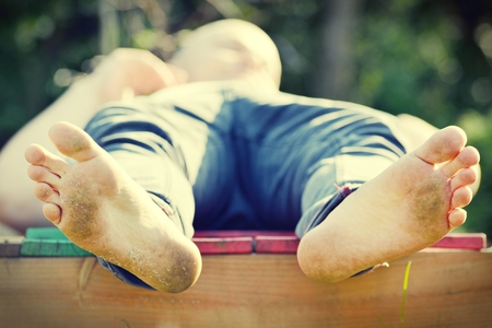 pieds sales: L'homme avec les pieds sales se trouve et se d�tend.