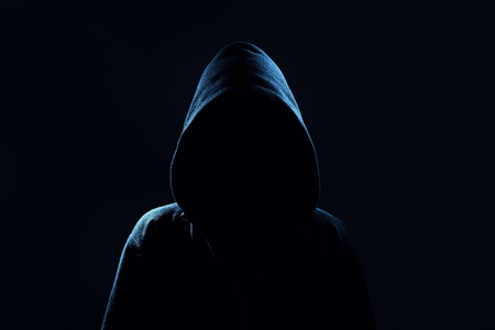 attacker: Mysterious, unknown person in the hood. Danger in darkness. Stock Photo