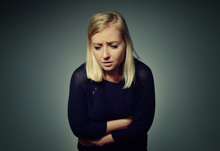 persona triste: Mujer con dolor en el abdomen.