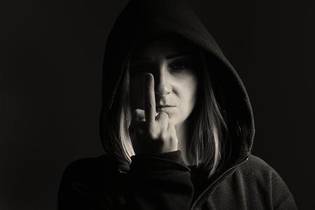 Mysteus vrouw in de kap toont teken van Fuck Off.