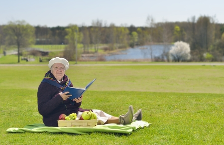Senior happy woman sitting on a blanket on glade in the park. She is reading book. Stock Photo