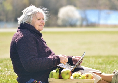 Senior happy woman sitting on a blanket on glade in the park. She is using a laptop.
