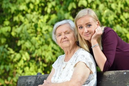 Babička a vnučka. Mladá žena pečlivě pečuje o starší ženu.