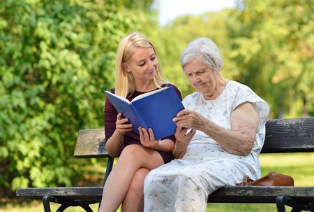 elder tree: Young woman reading a book elderly woman in the park.