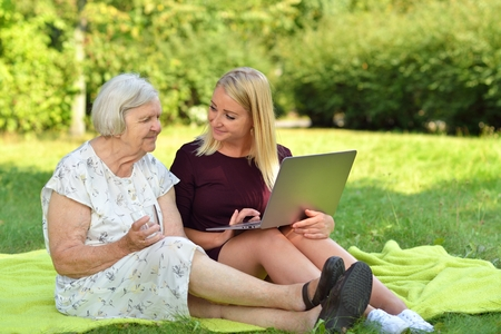 elderly woman: Young woman helping an elderly woman using the laptop in the park.