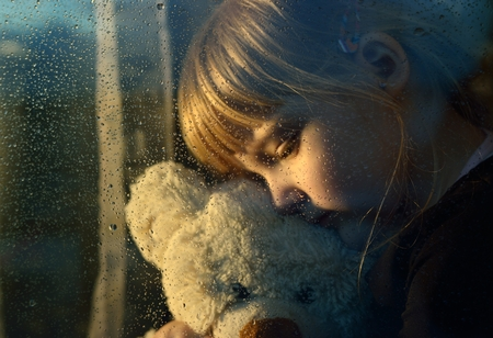 upset: Sad child hugs a plush toy at rainy window. Stock Photo