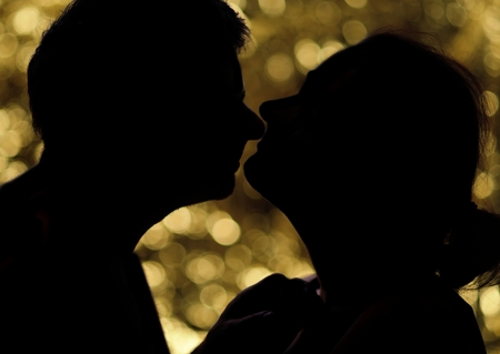 Man kissing woman on the golden circles background. photo