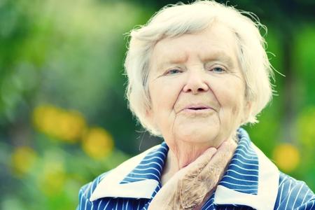 Senior happy woman smiling in garden.