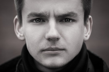 raised eyebrows: Black and white portrait photo of young man with sad look