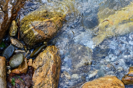 Water flowing over beautiful stones through the Italy Lake Como Banco de Imagens