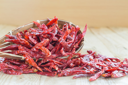dried chili in bamboo basket on wooden table Stock Photo